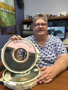 Cathy Zimmer holding a large tape reel used to store data.